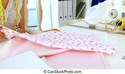 Designer cutting pink cloth with scissors in design studio