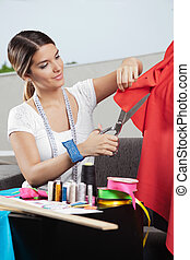 Designer Cutting Red Fabric - Young female fashion designer...