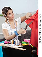 Designer Cutting Red Fabric - Young female fashion designer...
