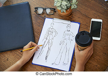 Designer drawing fashion sketch