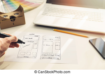 designer drawing website development wireframe on paper in office