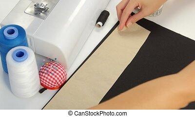 Designer draws a line on the fabric. Close up