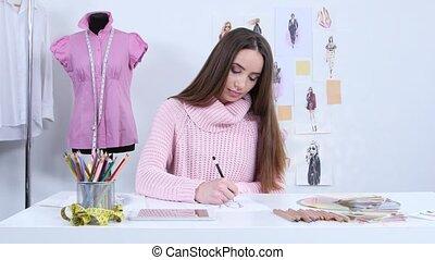 Designer draws sketches for a fashion magazine of women's...