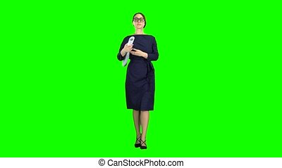 Designer girl comes with a drawing in her hands. Green screen