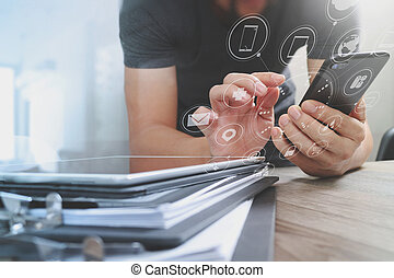 Designer hand using mobile payments online shopping, omni channel, in modern office wooden desk, icons graphic interface screen, eyeglass, filter