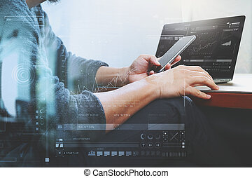 Designer hand using mobile payments online shopping, omni channel, laptop computer on wooden desk, digital screen graphic virtual icons, graph, diagram
