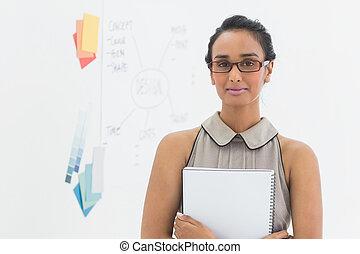 Designer holding notebook and smiling at camera