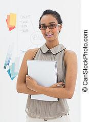 Designer holding notepad and smiling at camera