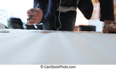 Designer in black jacket masterfully creates draft on sheet...