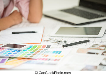 Interior designer's workplace with designer tools and color samples.