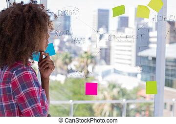 Designer looking at flowchart on window
