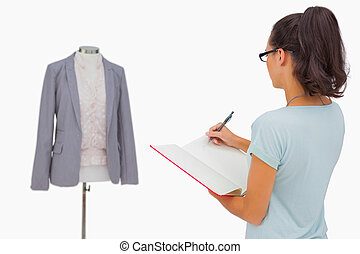 Designer looking at her mannequin and taking notes