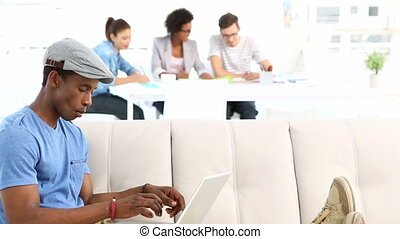 Designer lying on couch working on a laptop