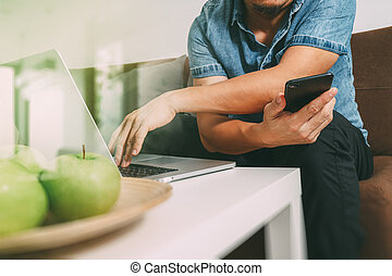 designer man hand using laptop compter and mobile payments online shopping,omni channel,sitting on sofa in living room,green apples in wooden tray,filter