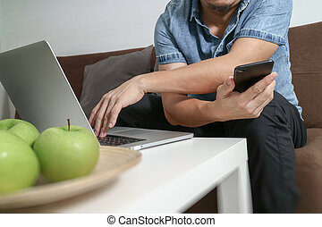 designer man hand using laptop compter and mobile payments online shopping,omni channel,sitting on sofa in living room,green apples in wooden tray