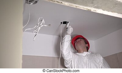 designer man making hole in ceiling plasterboard for ...