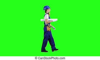 Designer of the construction site carries a drawing. Green...