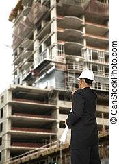 Designer Pointing At Building Under Construction