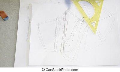 Designer shoes creates a sketch on the paper - Designer is...