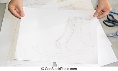 Designer shoes creates a sketch on the paper