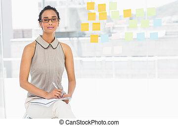 Designer taking notes and smiling at camera