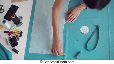 Designer using chalk for contouring pattern on blue fabric...