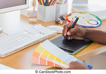 Designer using graphics tablet while holding colour charts