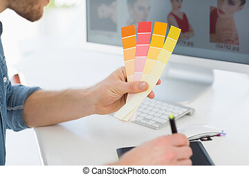 Designer working with digitizer holding colour chart at his...