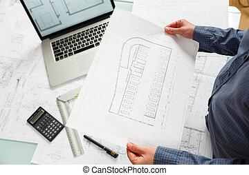 Designer works on a blueprint of new parking lot