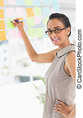 Designer writing on sticky notes on window smiling at camera