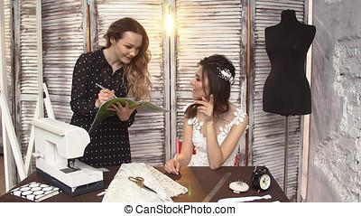 Designers draw sketches in the Studio. two attractive women working and smiling. Workspace designer.