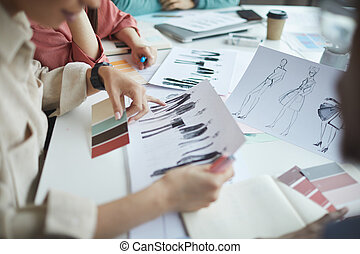 Close-up of designers sitting at the table and examining fashion sketches of clothes during meeting at office