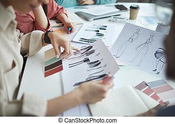 Designers examining fashion sketches - Close-up of designers...