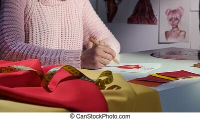 Designer's hands draw a sketch of a beautiful red dress. Close up