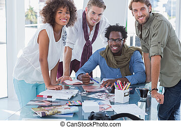 Designers smiling at camera in bright office