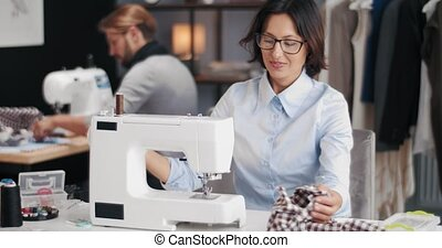 Attractive female designer smiling and looking at camera while her bearded partner tailoring clothing on sewing machine. Concept of fashion industry.