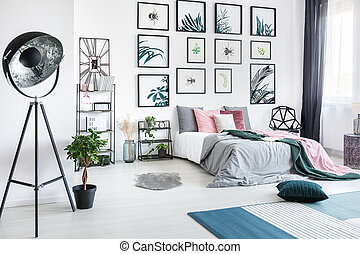 Designer metal lamp in spacious bedroom with plant and gallery of posters above king-size bed
