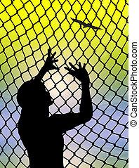 Desperate prisoner or refugee behind a fence longing for to live a free life
