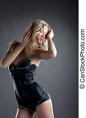 desired blond woman posing in leather corset
