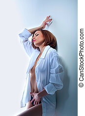 Desired young woman in sexy shirt on white wall