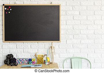 Desk and blackboard in creative room