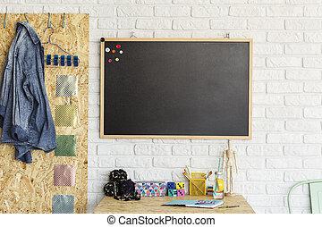 Desk and blackboard in modern room