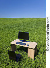 Desk and Computer In Green Field With Blue Sky