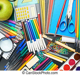 Desk covered with multiple stationery - Black desk's surface...