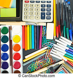 Black desk's surface covered with multiple stationery office supplies as a background back to school composition, top view above