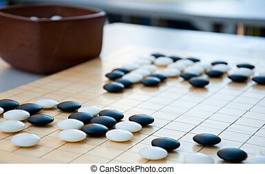 Desk for board game Go and black and white bones on table. Go or wei-Chi - traditional chinese board game