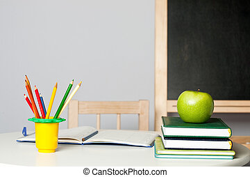 Desk in classroom - Desk with apple, pencil, notebook and...