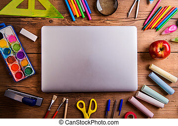 Desk, school supplies, closed notebook, wooden background
