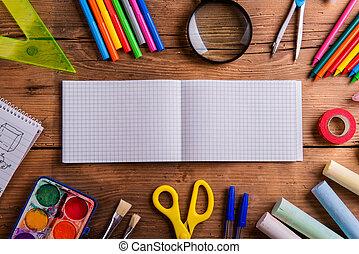 Desk, school supplies, squared paper, wooden background