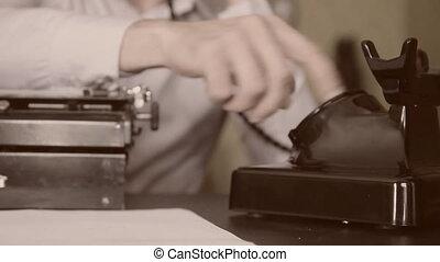 Desk. Vintage typewriter, old phone. Sepia